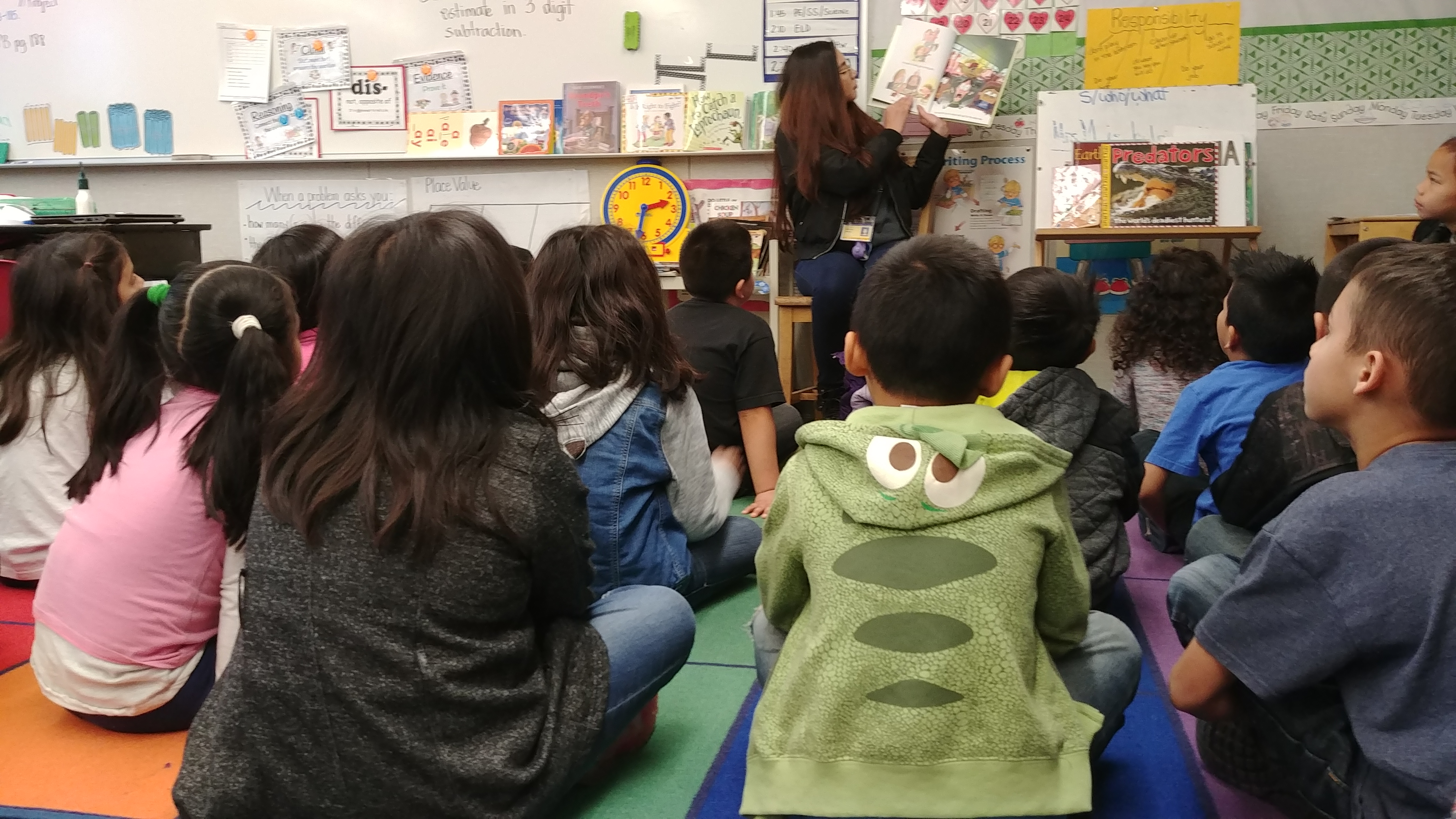A volunteer reading to a classroom of children
