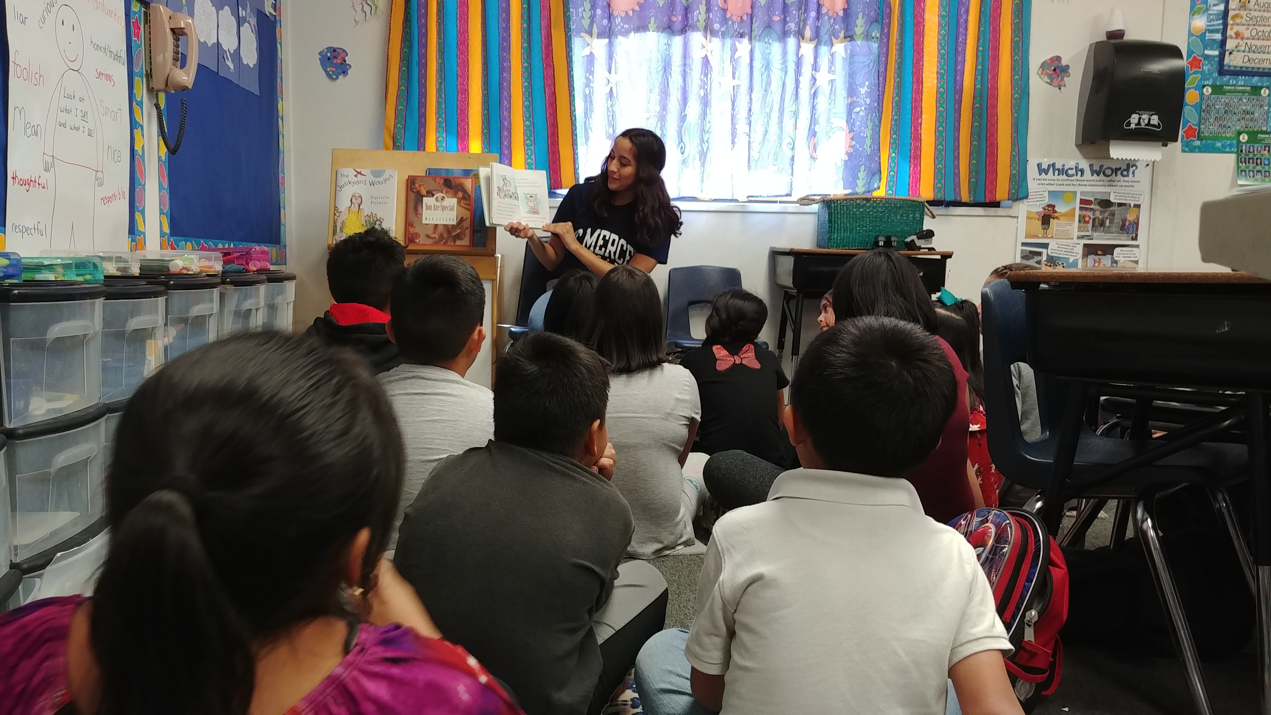 A volunteer reading to a class of children